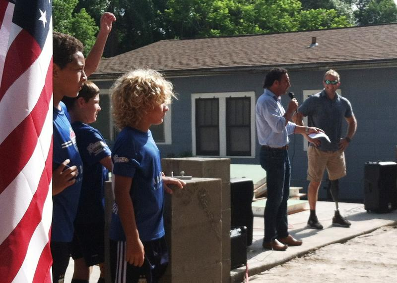 """Members of the Tampa Bay United youth soccer team stand by as their coach, Martin Gramatica, introduces combat veteran Justin Lansford standing on the foundation of his future """"mortgage free"""" home."""