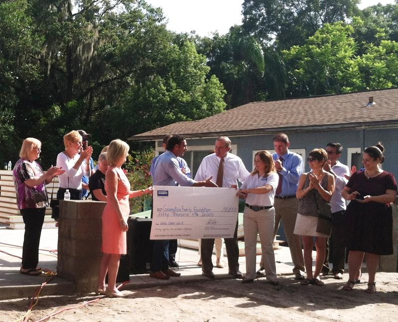 A $50,000 check from a walk-a-thon is presented to help pay for the new home..