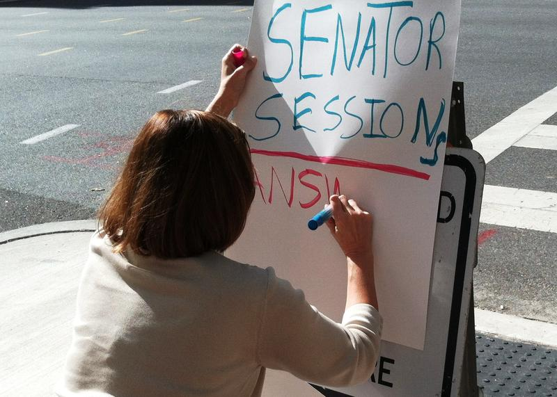 On her lunch break in downtown Tampa, Michelle Kenoyer quickly pens her protest sign to join others demonstrating against attorney general nominee Alabama Sen. Jeff Sessions.