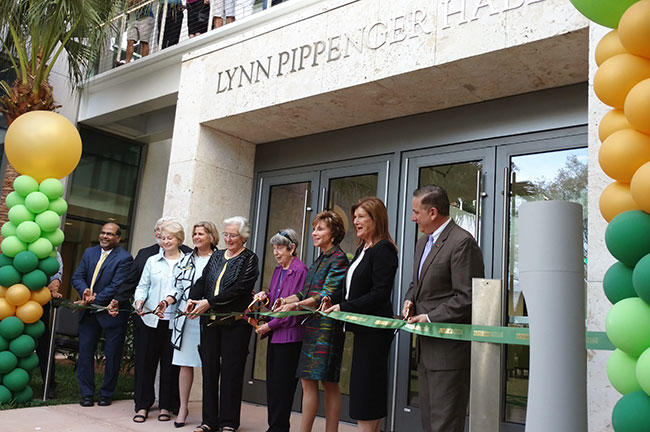 Officials from USF and USF St. Petersburg are joined by city and local officials, as well as Kate Tiedemann (5th from left in black) and Lynn Pippenger (next to her in purple) in cutting the ribbon on Pippenger Hall.