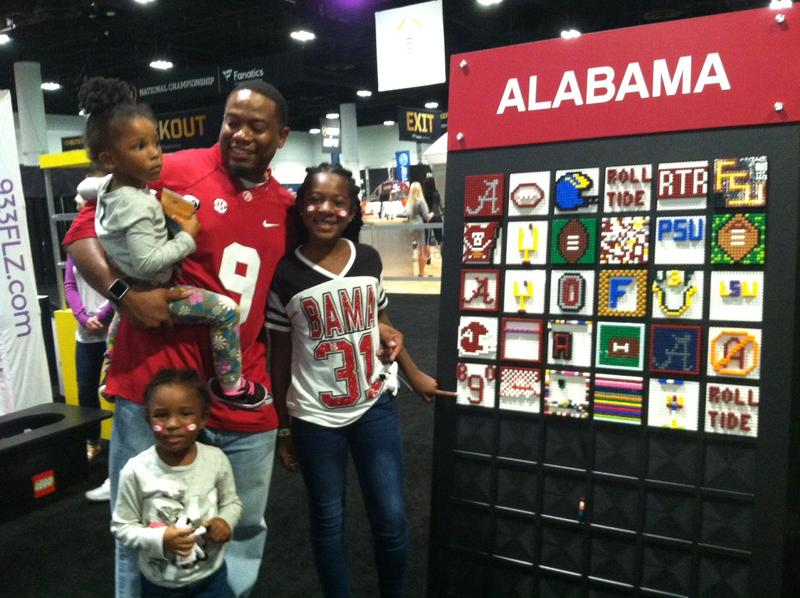 Alabama fans pose by their Lego board contribution.