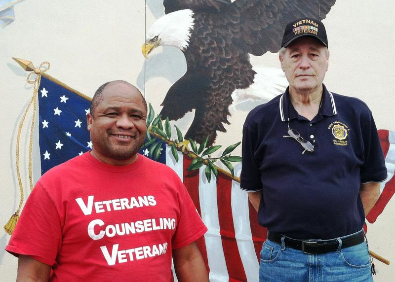 "Army veteran Ellsworth ""Tony"" Williams and Air Force veteran G.W. ""Bill"" Hamblin standing in front of the mural outside American Legion Post 5 in Tampa."