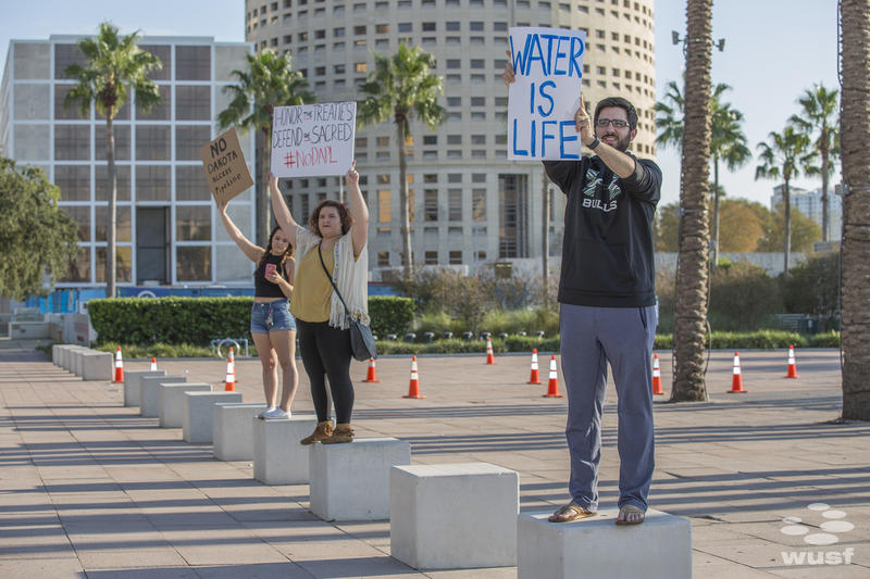 Water protectors hold up signs at Curtis Hixon Waterfront Park.
