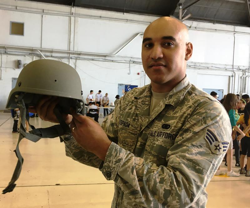 MacDill Airman Christian Espada assisted students trying on field gear like combat helmets.