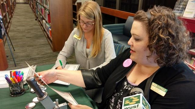 "USF Humanities Institute Director Liz Kicak (right) creates a ""Shakespearean insult button."" Her favorite creation of the day: ""Lumpish onion-eyed hugger mugger"""