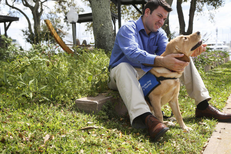 Anthony Loffler poses with his yellow Lab Jennings. The pup is a guide dog in-training.