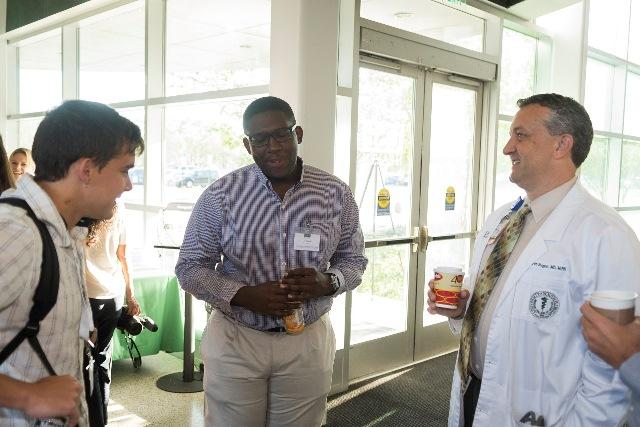 PA student Jensen Jozil (center) talks to program director, Dr. Todd Wills (right) and fellow students at orientation.