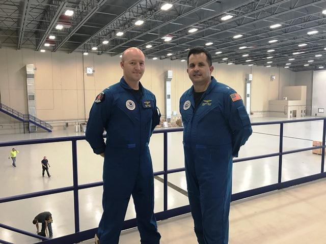 Captain Michael Silah and Lieutenant j.g. Billy Bonner stand in the massive hangar at the Aircraft Operation Center's new home in Lakeland.