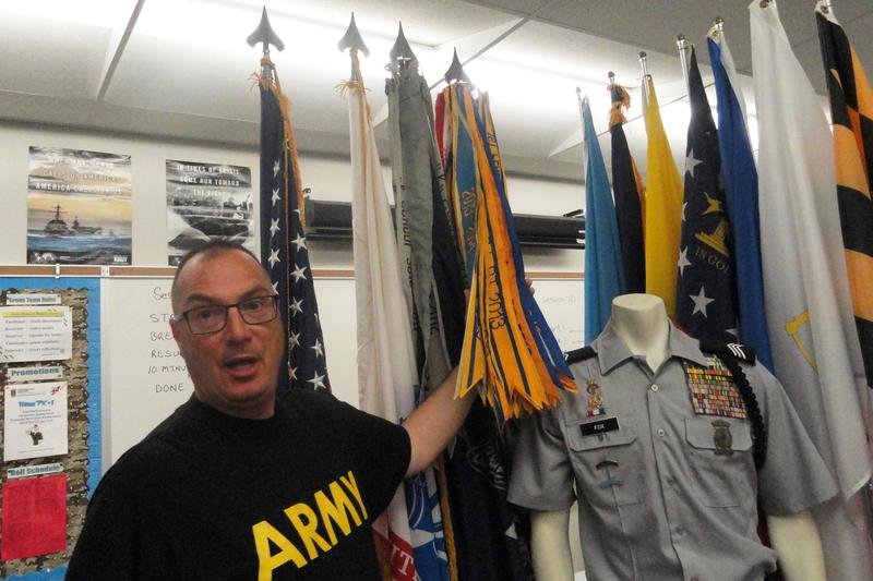 Newsome High JROTC instructor, retired Lt. Col. Mo Buldoc points out the display of ribbons and flags that adorn their computer lab and classroom.