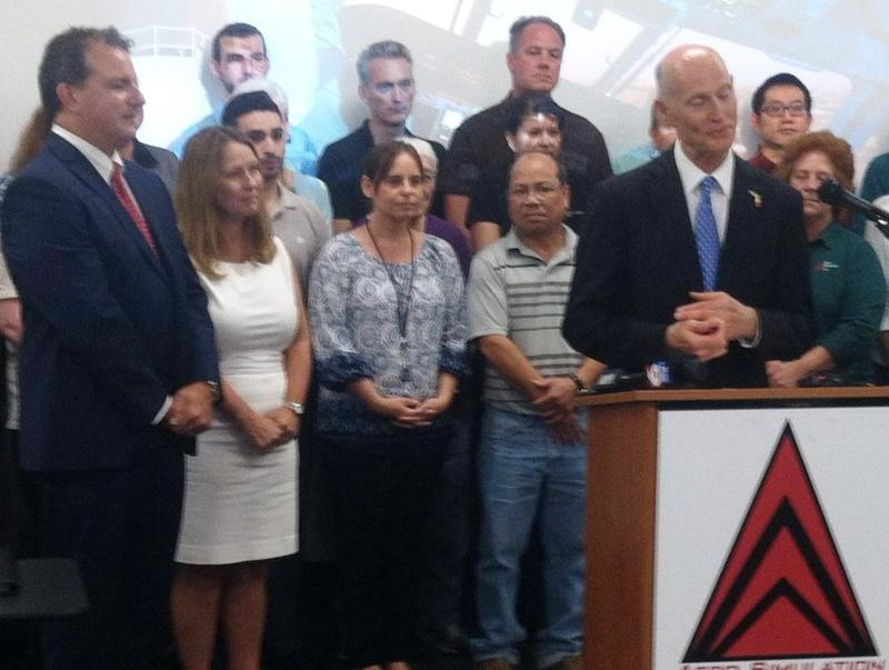 Jimmy Patronis, left, his wife Katie and Gov. Rick Scott during an appearance at Aero Simulation in Tampa.