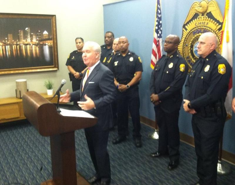 Tampa Mayor Bob Buckhorn speaks in front of retiring Chief Eric Ward and Interim Chief Brian Dugan, right