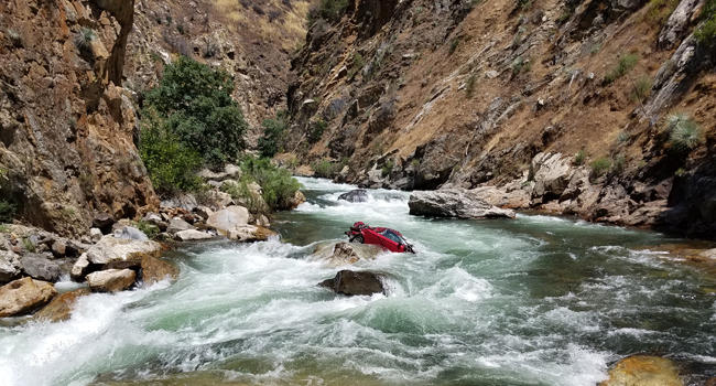Officials say the car went off the road 75 miles east of Fresno in the steep Sierra Nevada mountains and crashed 500 feet below into the Kings River.