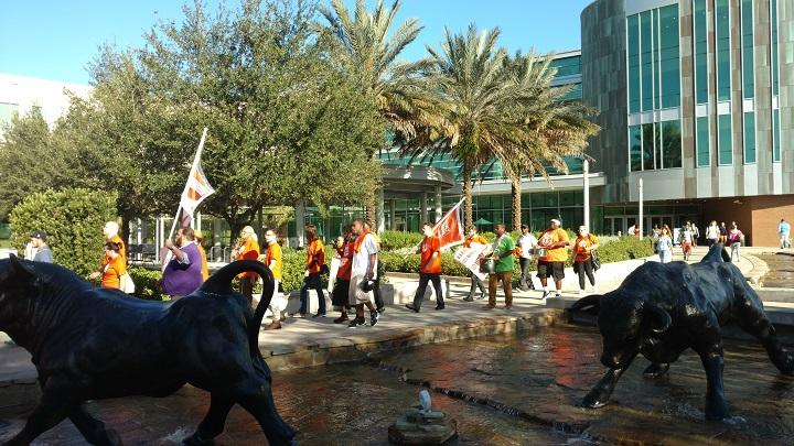 Adjunct faculty and supporters march outside the USF Marshall Student Center in Tampa Thursday.