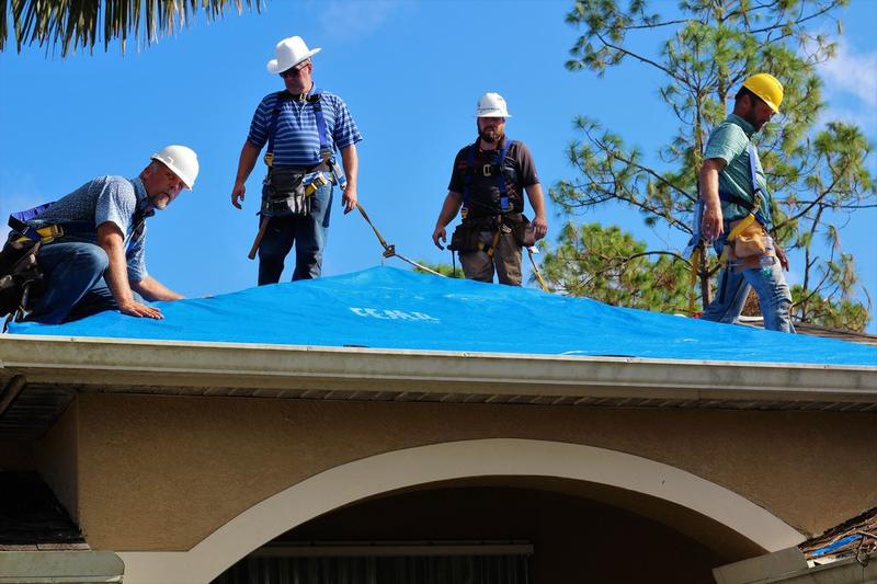 Roofing contractors of S & M Associates apply and affix FEMA supplied blue tarp sheets onto a local Naples, Florida home in order to provide a temporary solution for residence housing shelter and prevent further damage.