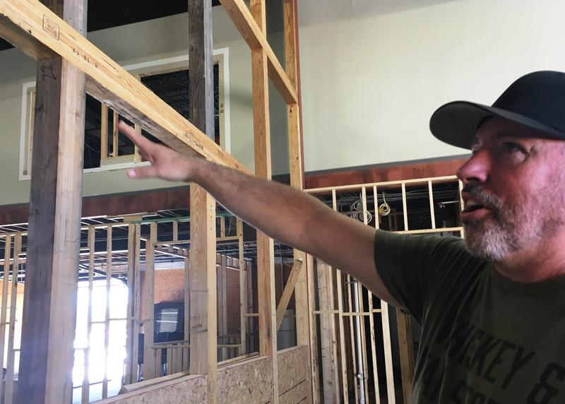 Former Green Beret Scott Neil points to the framework for the glass wall that will separate the American Freedom Distillery from the restaurant under construction.