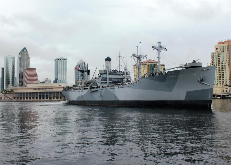 The American Victory Ship cruising along the channel with the Tampa Convention Center and Skyline in the background.