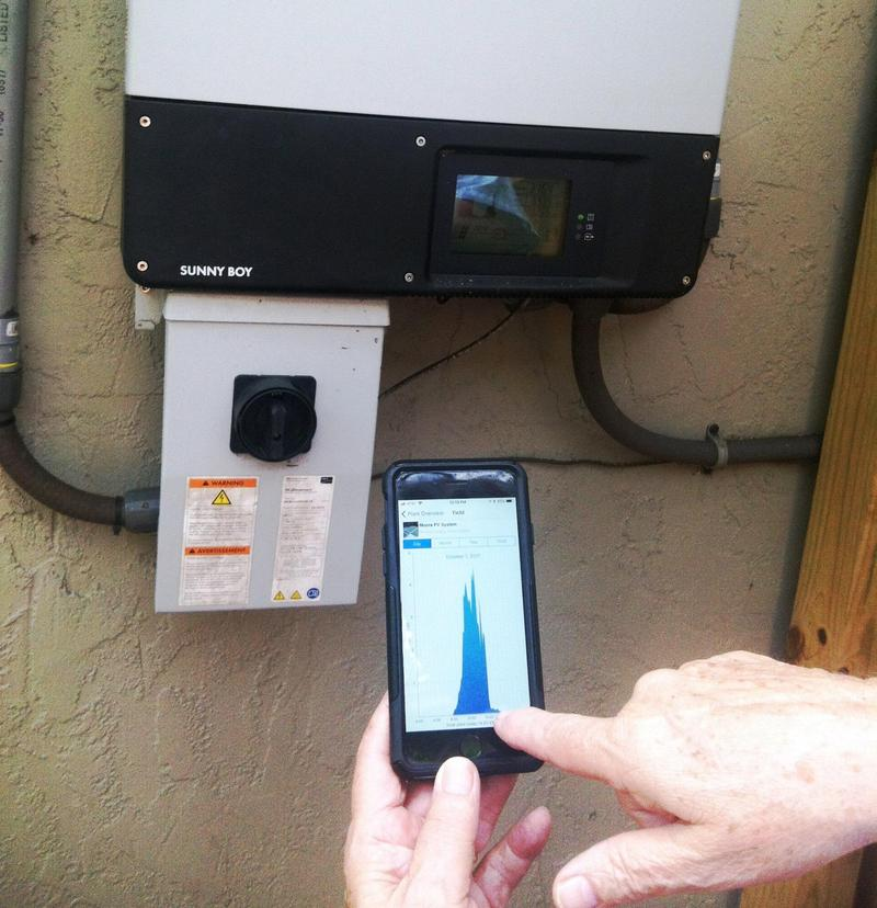 Solar customer reads information from his meter to track how much energy his panels are generating.
