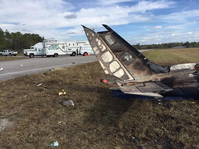 The burned tail of a Cessna 340 twin-engine plane after it crashed Sunday morning at Bartow Municipal Airport, killing 5 people.