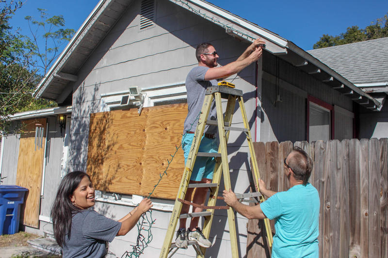 Volunteers with the organization Light the Heights decorate Donna Bradley's Seminole Heights home.
