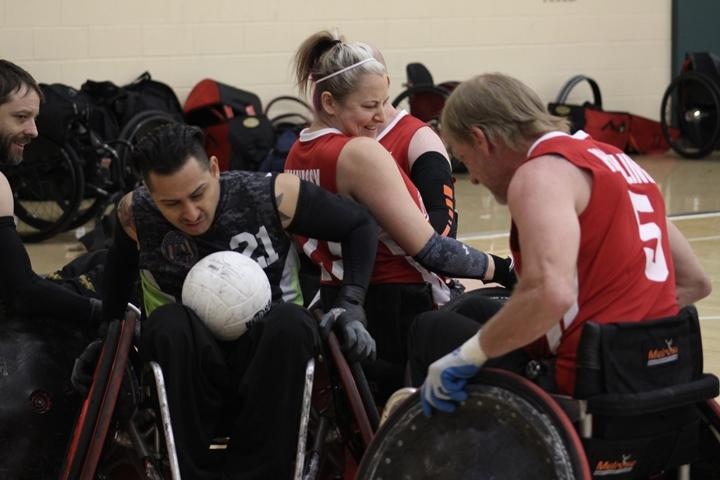 Wheelchair rugby players try to carry a modified volleyball across an end zone without getting rammed into or jammed up.