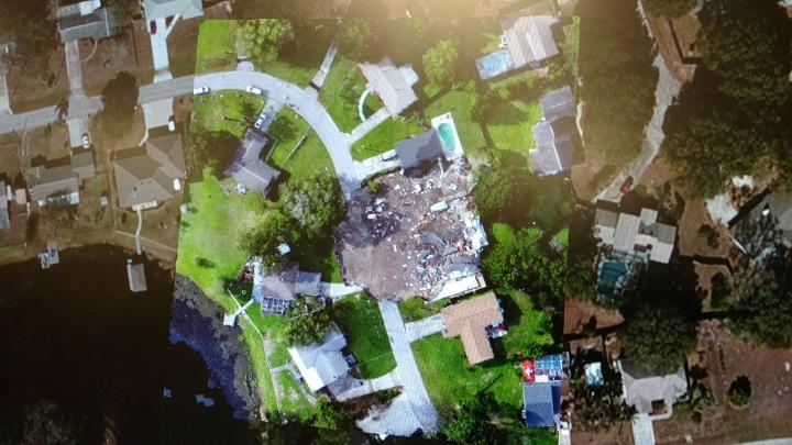A map showing, through processed drone imagery, a Pasco County sinkhole as seen in July 2017.  The darker homes on the left and right are taken from images before the sinkhole opened.