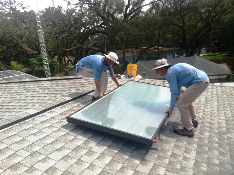 Workers install solar panels on a Temple Terrace resident's home.
