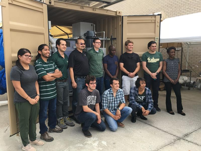 USF engineering students stand in front of the NEWgenerator with Dr. Daniel Yeh (back row in sunglasses) and Lindelani Xaba (back row, fourth from right).