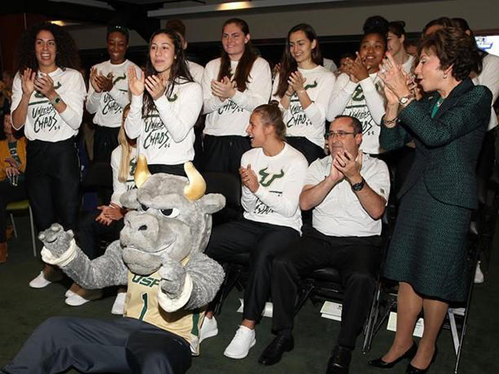 The USF women's basketball team, coach Jose Fernandez and USF System President Judy Genshaft celebrate following the announcement that the team made the NCAA Tournament for a fourth year in a row in Tampa Monday night.