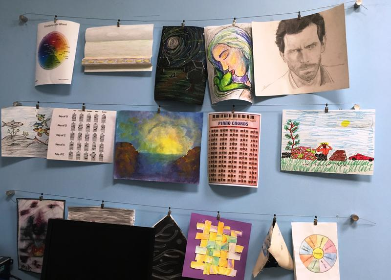 A gallery of veterans' artwork from therapy sessions hangs above the computer that connects with veterans in the Creative Arts Therapy program at the Malcom Randall VA Medical Center in Gainesville, FL.