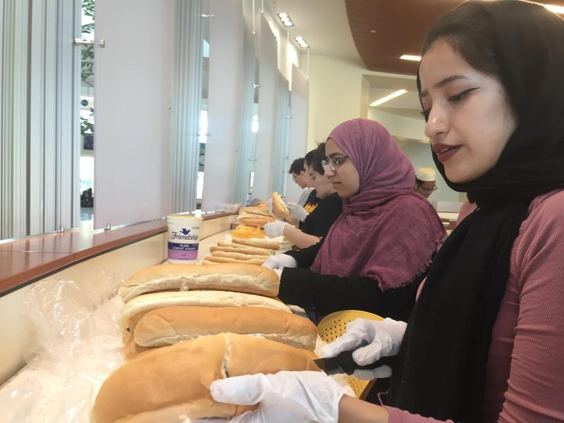 Yasmeen Alkishawi, the president of Project Downtown Tampa, is seen slicing bread as she and other organization members work in an assembly line to make turkey sandwiches for the homeless.