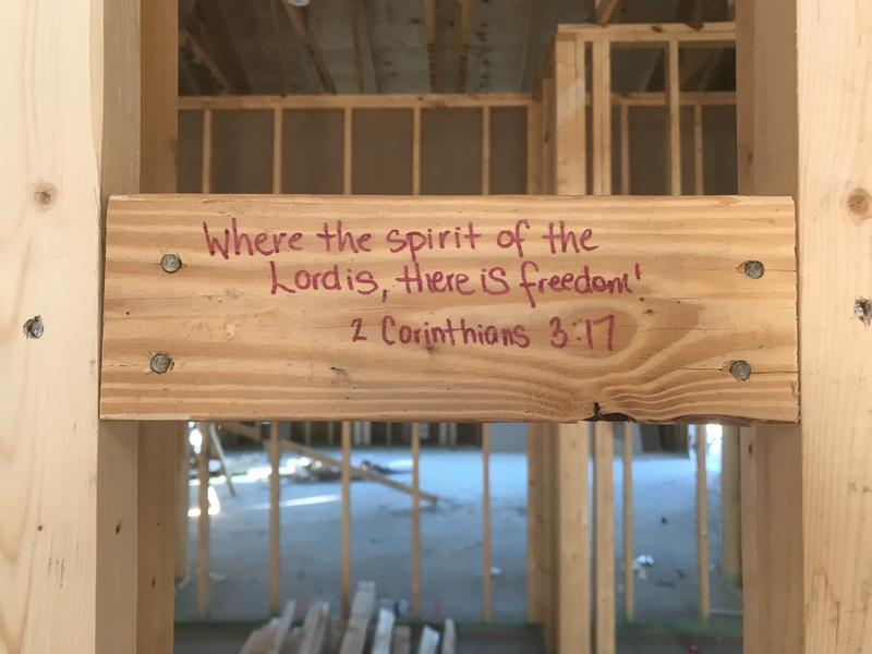 This Bible verse is one of many decorating the hidden beams of each house on a safe campus community for child victims of sex trafficking.