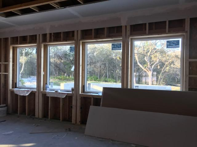 Large windows in each house look out into a quiet, wooded area.