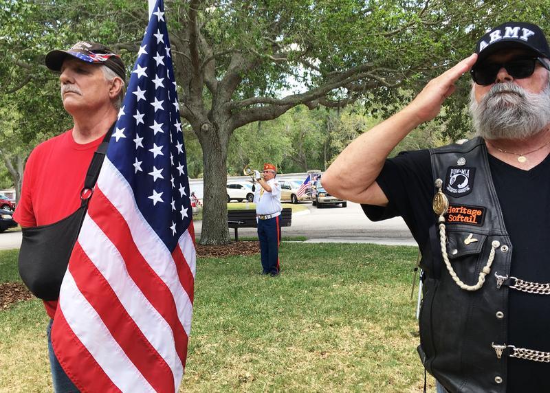 A bugler plays Taps as veterans salute.