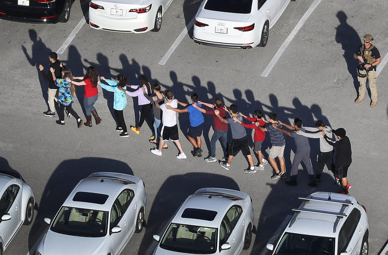 Students are brought out of the Marjory Stoneman Douglas High School in Parkland after a gunman opened fire