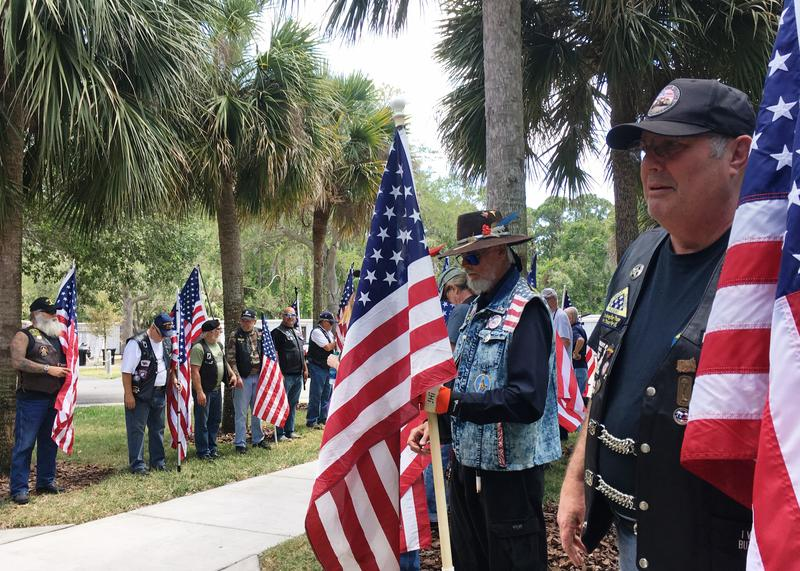Veterans line the walkway holding flags for the duration of the Unattended Ceremony at Bay Pines.