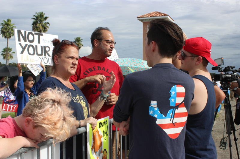Protester Susan Stearns, left, talks with Trump backers outside the expo hall.