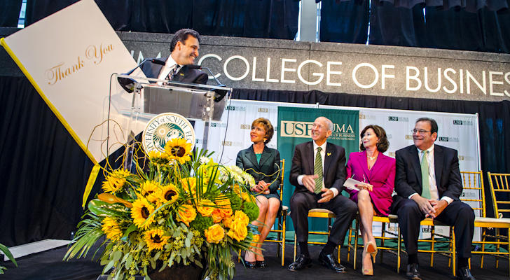 USF Muma College of Business Dean Moez Limayem with a 'thank you' card for Les & Pam Muma, center, at the College renaming ceremony in Oct. 2014. Les Muma will head the search committee for the successor to USF President Judy Genshaft, in green.