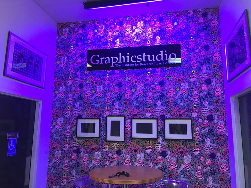 Graphicstudio features a back wall covered in wallpaper with fluorescent ink. When in front of a black light and looked at through 3D glasses, the wallpaper looks three dimensional. It was created by Trenton Doyle Hancock