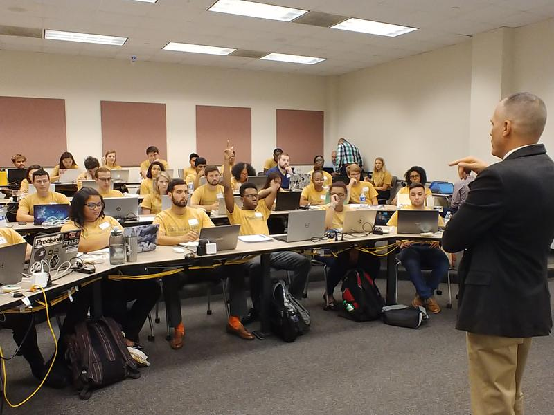 USF Muma College of Business instructor Clinton Daniel speaks to students at the first session of the ReliaQuest Cybersecurity Labs at the USF Muma College of Business Oct. 5 in Tampa.
