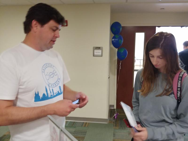 Eric Tarbill of event sponsor, The Council on International Education Exchange, shows potential study abroad programs to USF Tampa senior Kathryn Kochinski.
