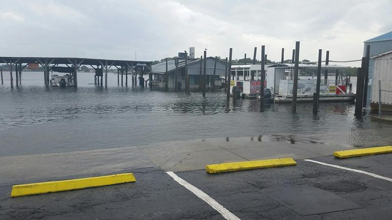 Water crests over a sea wall into a parking lot in Crystal River in Citrus County.