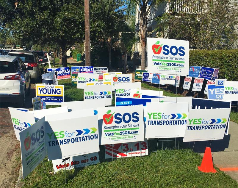 Signs advocating positions in the upcoming Hillsborough tax referendums outside the West Tampa library
