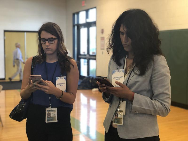 Interns Bethany Tyne, left, and Jessica Barron tweet out information for WUSF News at a Democratic party rally in Oct. 2018.