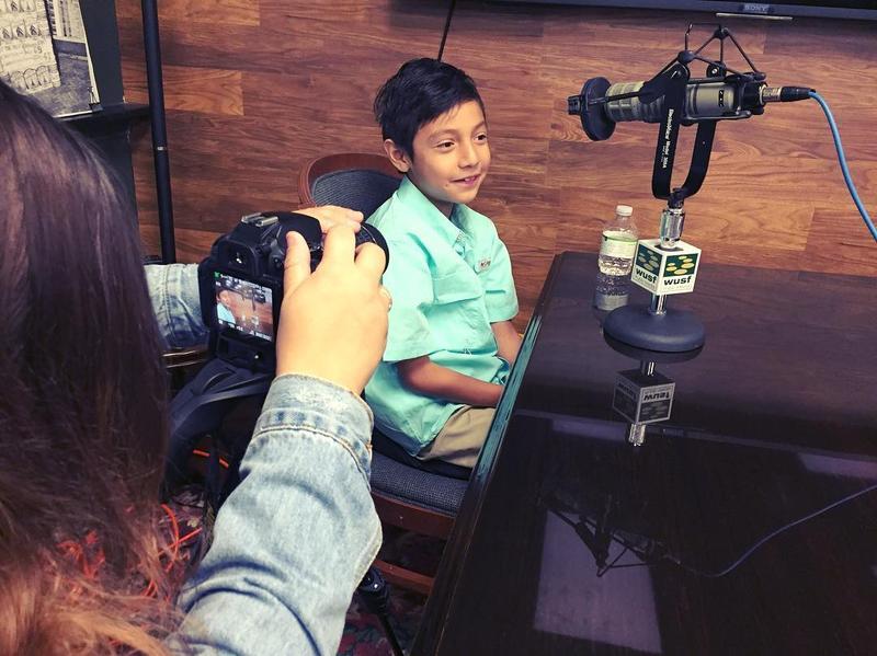 Junior Archivist Jaden Felix is interviewed while USF student journalist Yara Zayas takes his picture.
