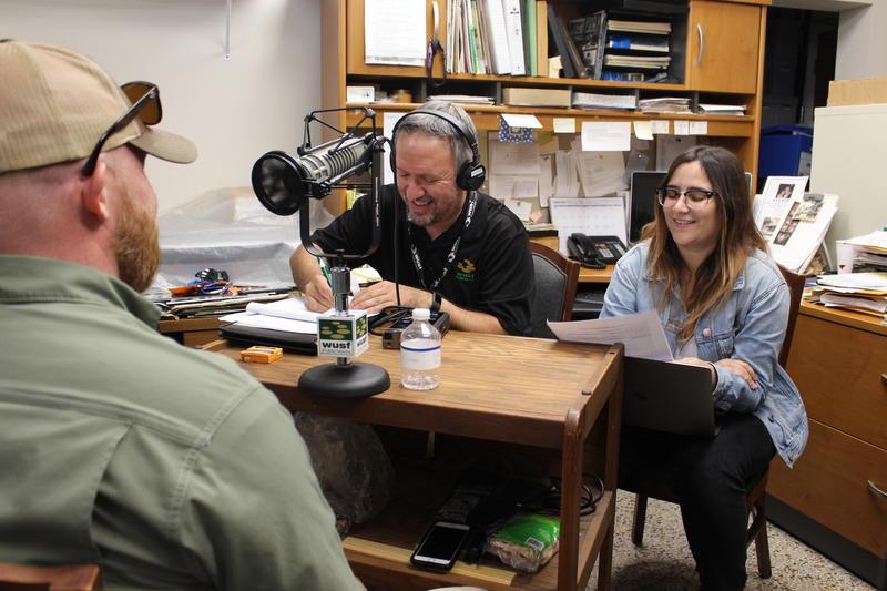 Johnson's Barbecue owner Owen Johnson, left, talks to WUSF's Mark Schreiner and USF student journalist Yara Zayas.
