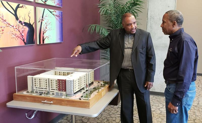The Tampa Housing Authority's Leroy Moore (l) points out a model of the Ella to State Sen. Darryl Rouson (D-19) inside the building's community room. He says the THA has the capacity to build more senior housing, but needs more funding to make it happen.