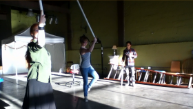 Cyclopaedia cast members rehearse a dance that involves swinging long, white pipes to create percussion sounds.
