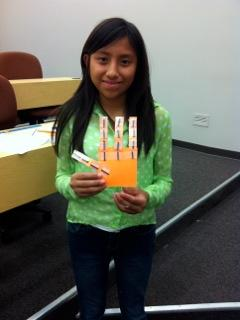 Samantha Bautista holding her robotic hand.  The girls learned the fundamentals behind designing a robotic hand and were able to build these models to move each finger independently and by finger joints.