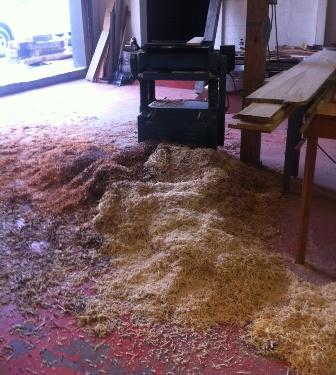Wood shavings rest on the floor beneath a planer at the Chattanooga Woodworking Academy.