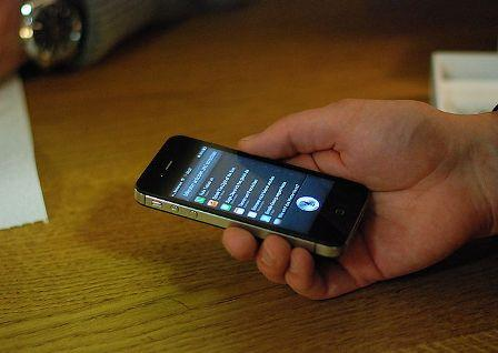 An iPhone user talks to Siri, a feature that follows voice commands.